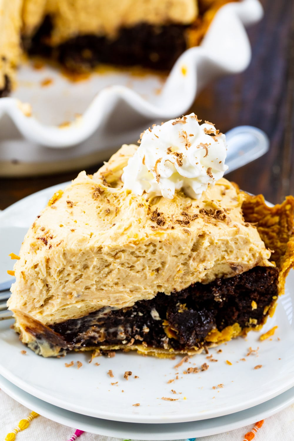 Peanut Butter Brownie Pie slice topped with whipped cream on plate.