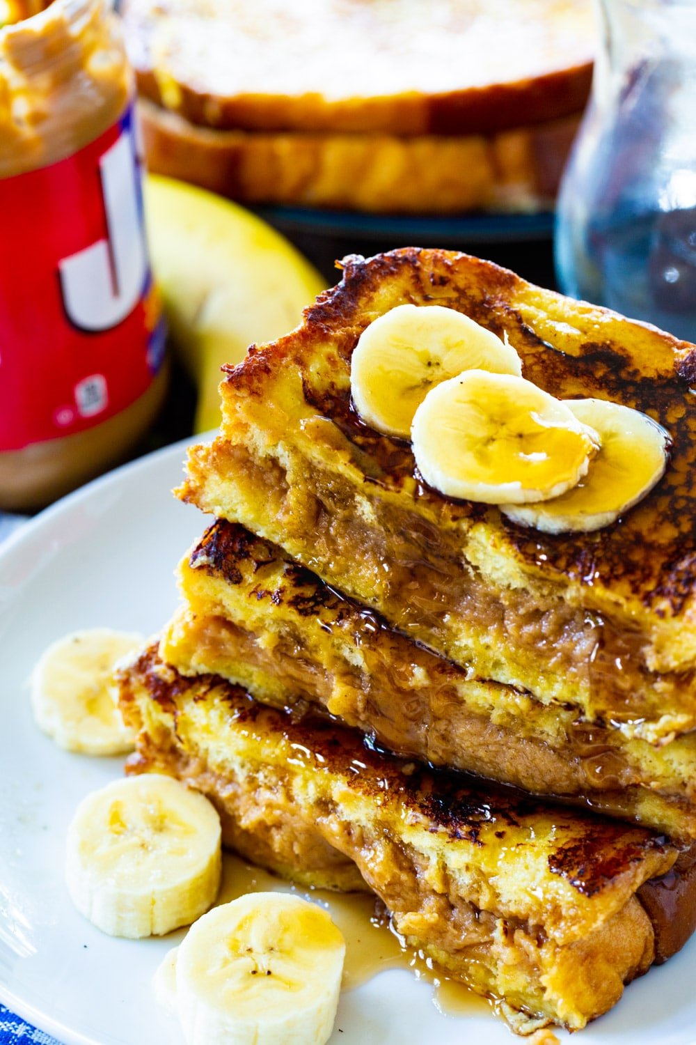French Toast topped with banana slices on a plate.