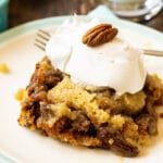 Slice of Pecan Pie Cake topped with whipped cream.