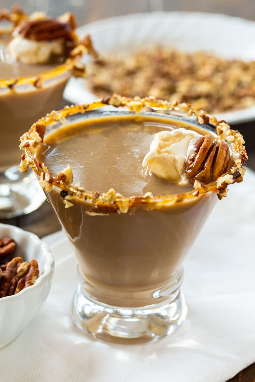 Pecan Pie Martini with plate of chopped pecans in background.