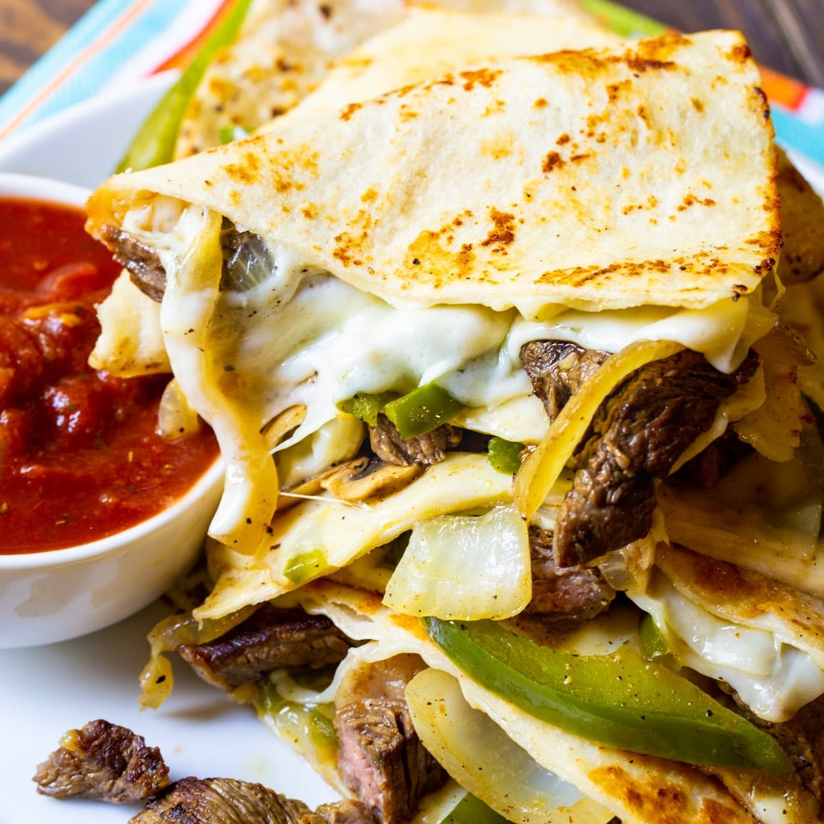 Trinagles of Philly Cheese Steak Quesadilla piled up on plate with bowl of salsa.