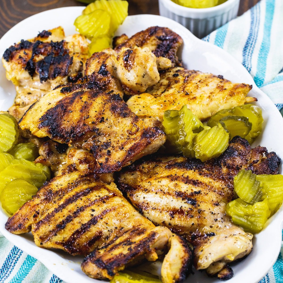 Pickle-Brined Grilled Chicken on a serving platter with pickle chips.