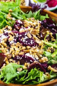 Pickled Beets Salad with Walnuts and Feta in a wooden bowl.