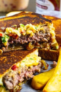 Patty Melt cut in half with fries.