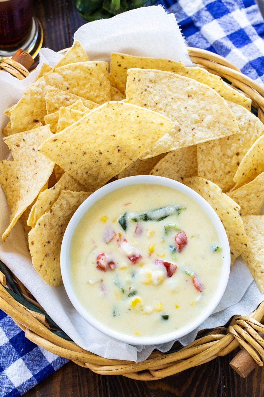 Queso in a small ramekin surrounded by tortilla chips.