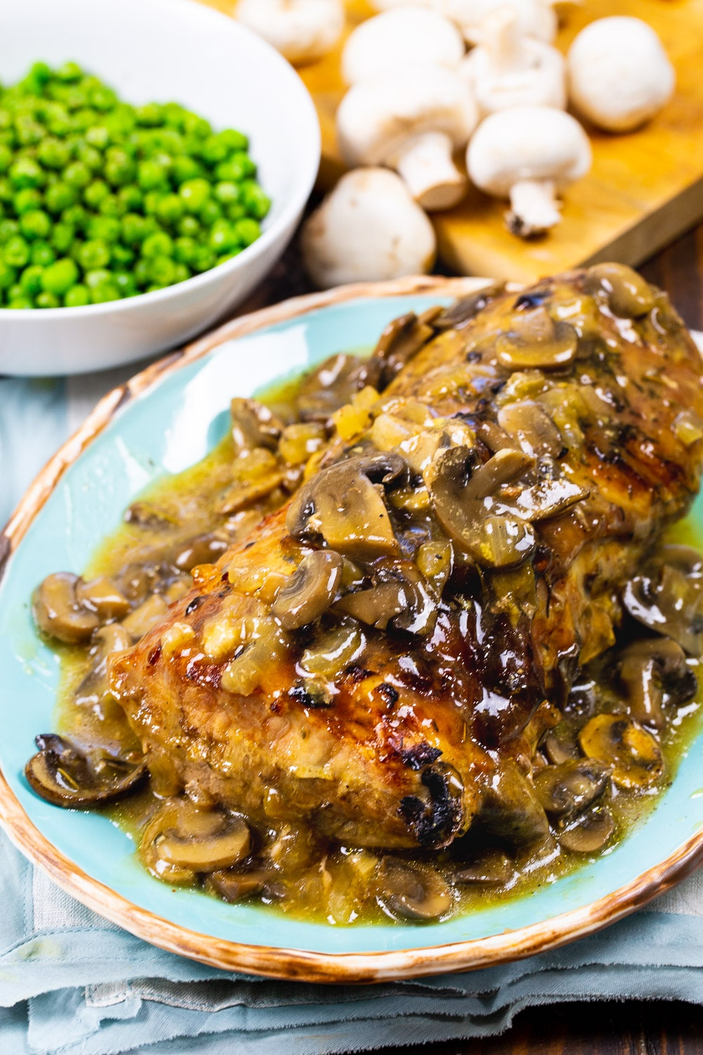 Roasted Pork Loin with Mushroom Gravy on serving platter with bowl of peas.