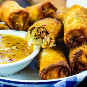 Pulled Pork Egg Rolls in serving tray with peach dipping sauce.