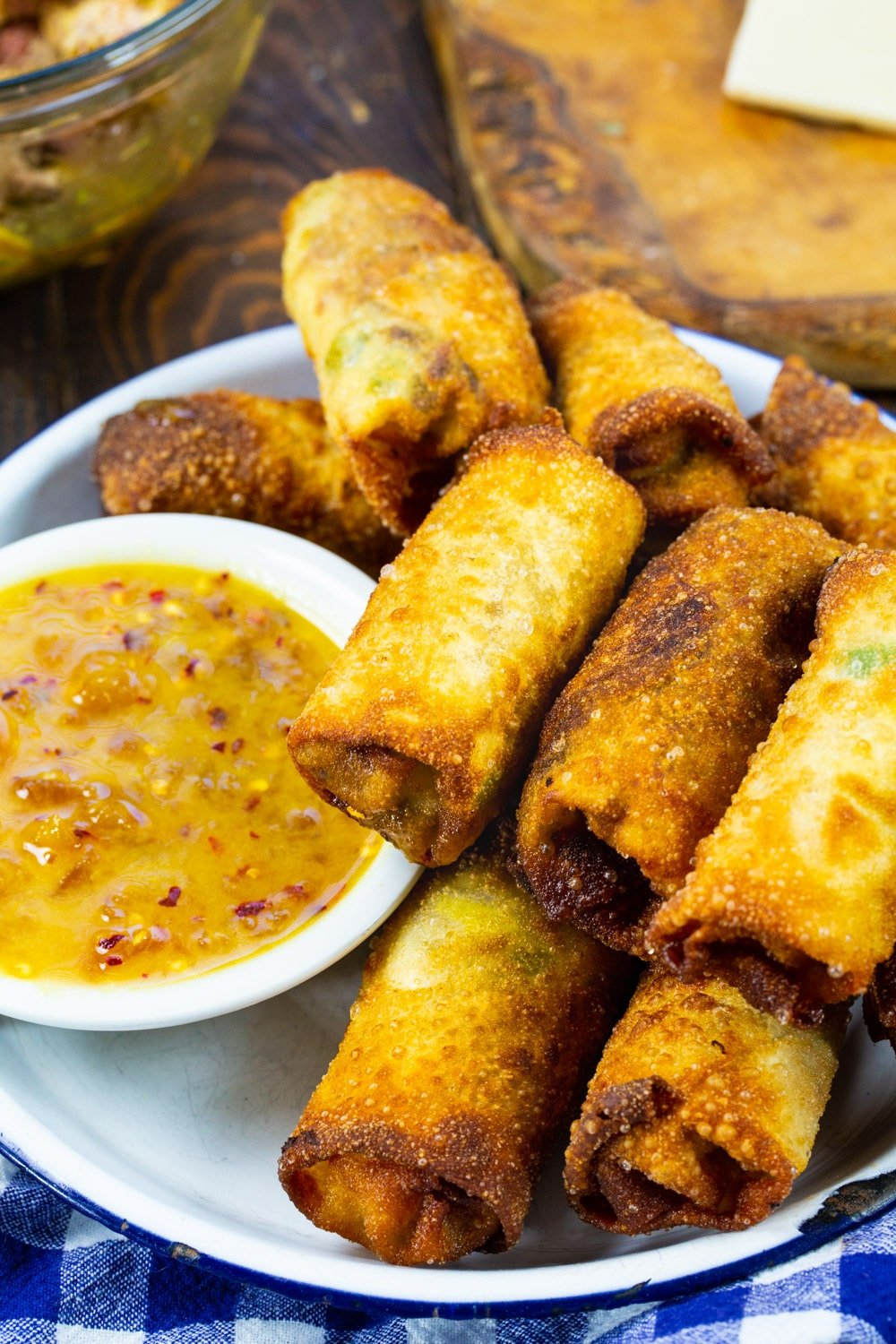 Pulled Pork Egg Rolls in serving tray with bowl of dipping sauce.