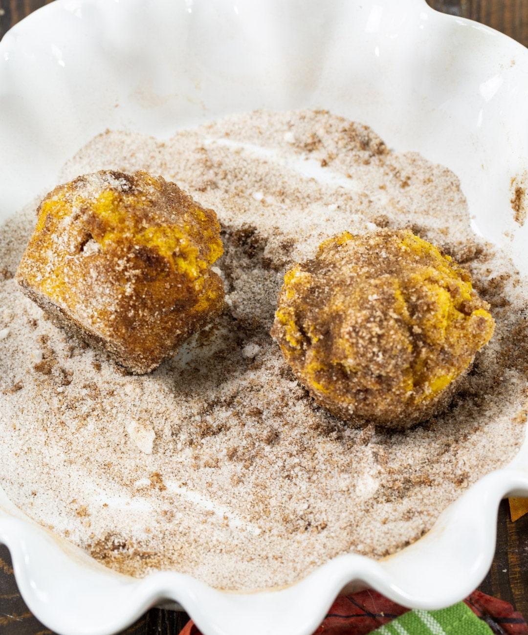Muffins getting coated in cinnamon sugar.