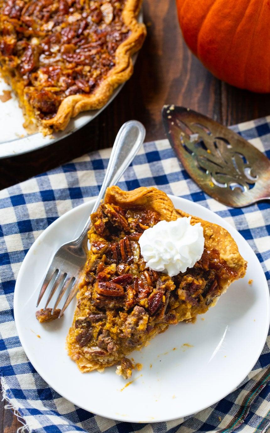 Overhead of slice of Pumpkin Pecan Pie with the rest of the pie beside it.