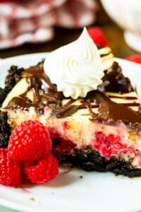 Slice of Raspberry Cream Cheese Pie on a plate with raspberries.
