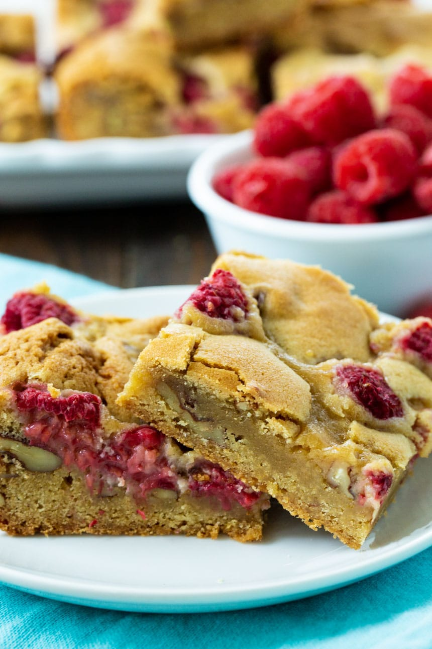 Raspberry Pecan Blondies on a plate with more blondies and raspberries in background.