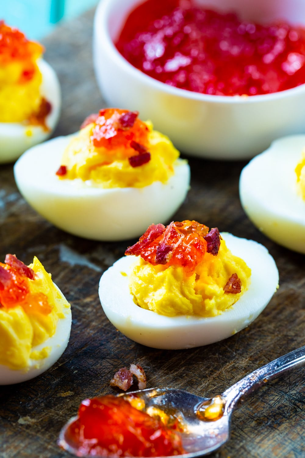 Red Pepper Jelly Deviled Eggs with Bacon with a bowl of pepper jelly.