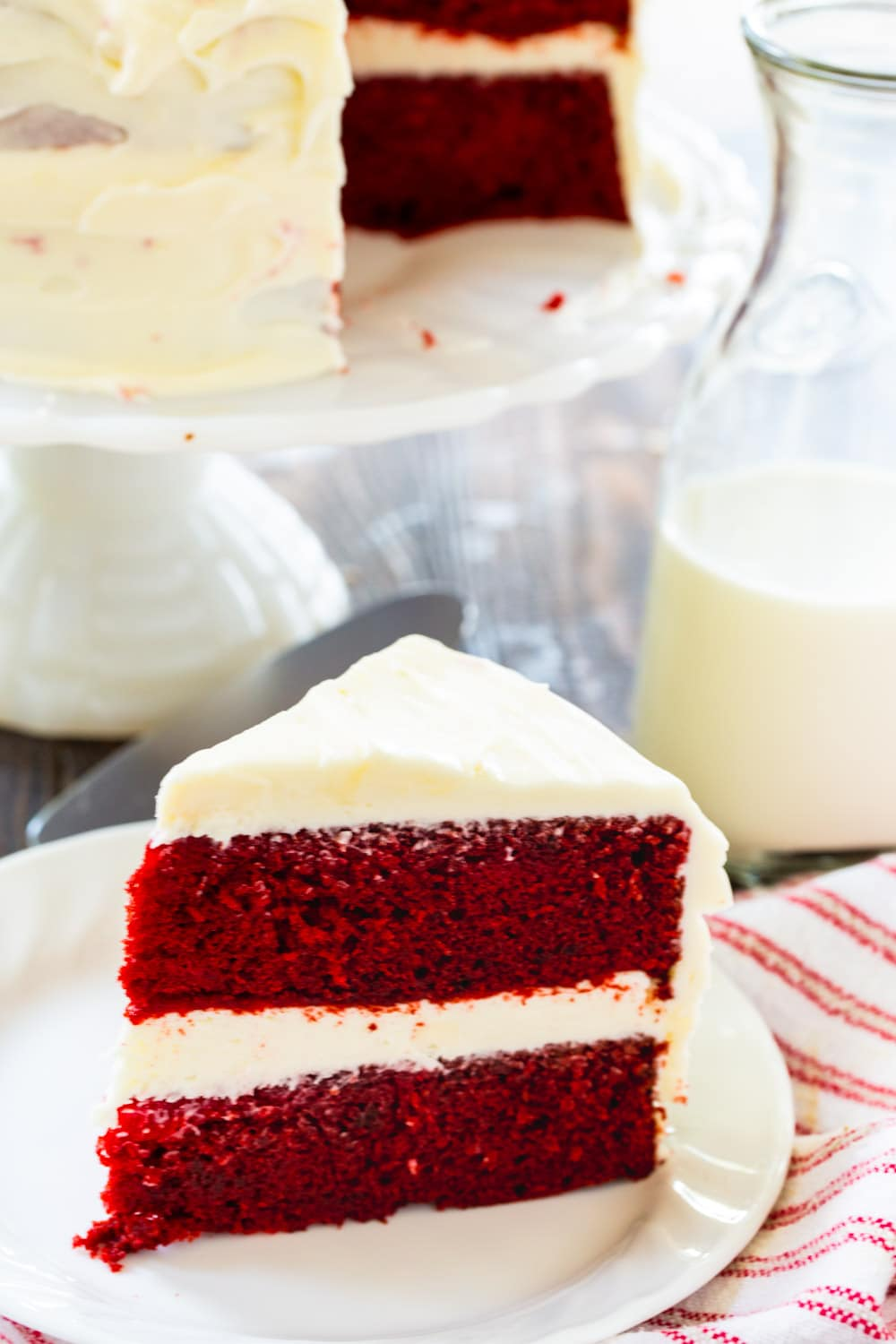 Slice of cake on plate with rest of cake on cake stand in background.