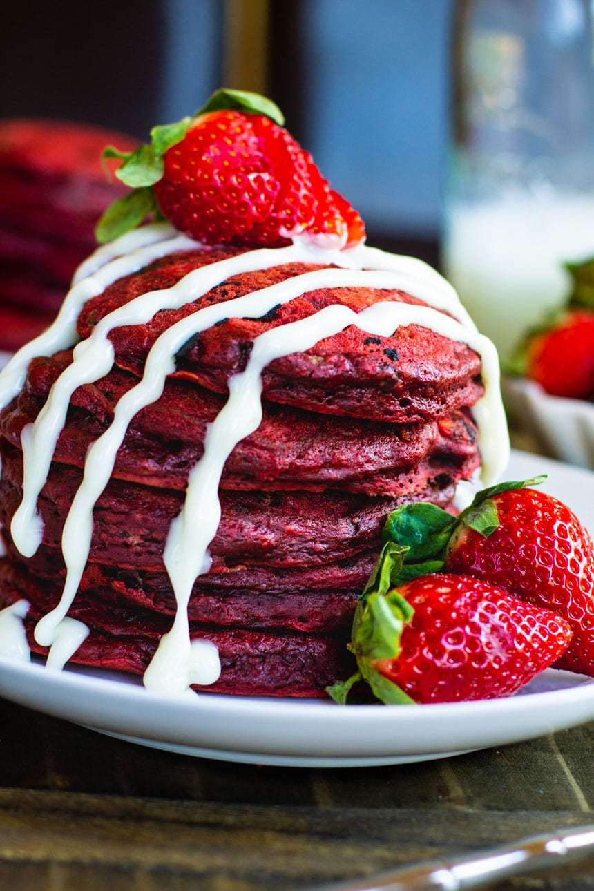 Red Velvet Pancakes with fresh strawberries and a cream cheese drizzle.