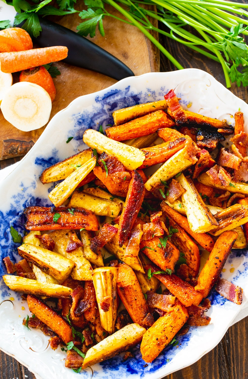 Roasted Carrots and Parsnips on platter with fresh carrots and parsnips next to it.