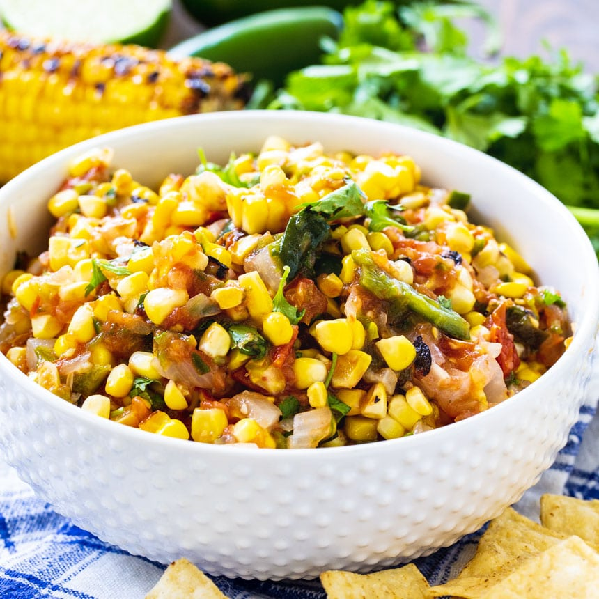 Corn salsa in a white bowl surrounded by tortilla chips and cilantro.