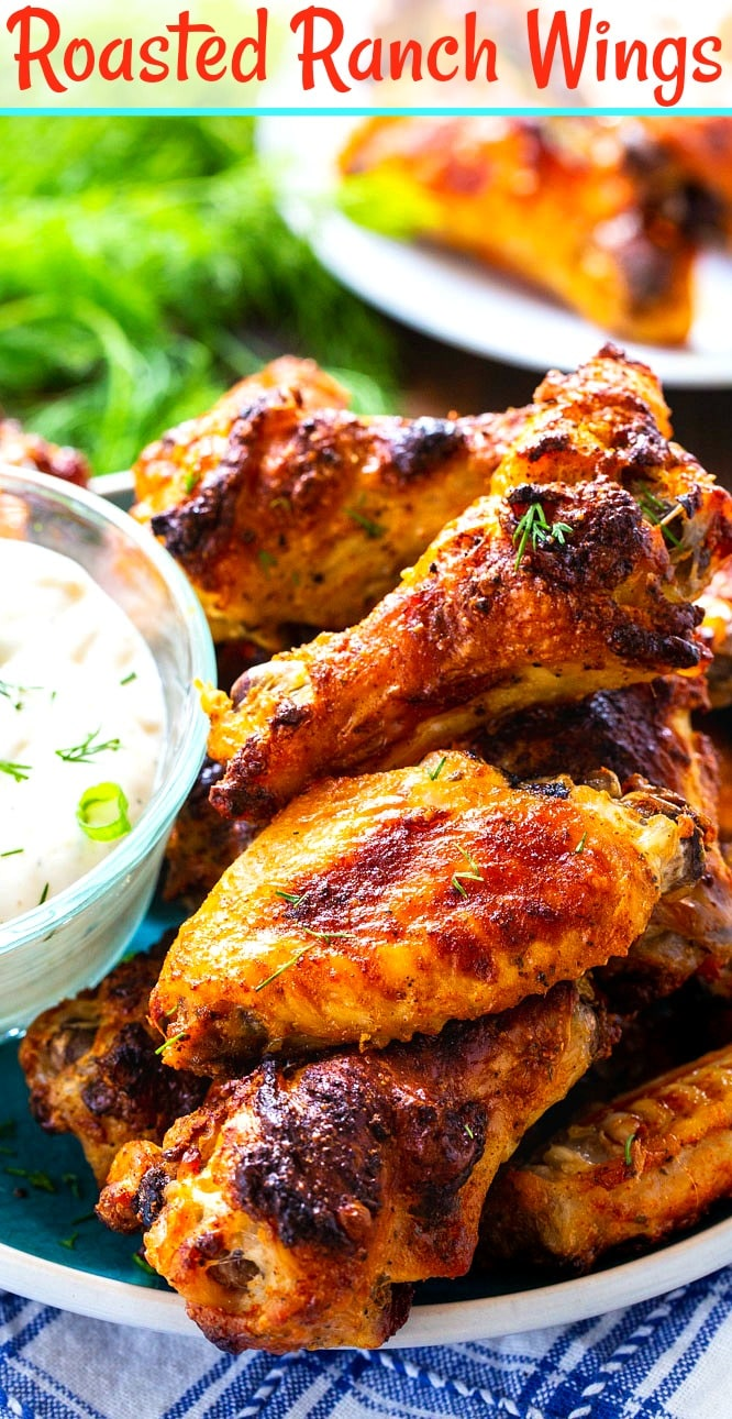 Close-up of wings piled up on plate with bowl of RAnch.