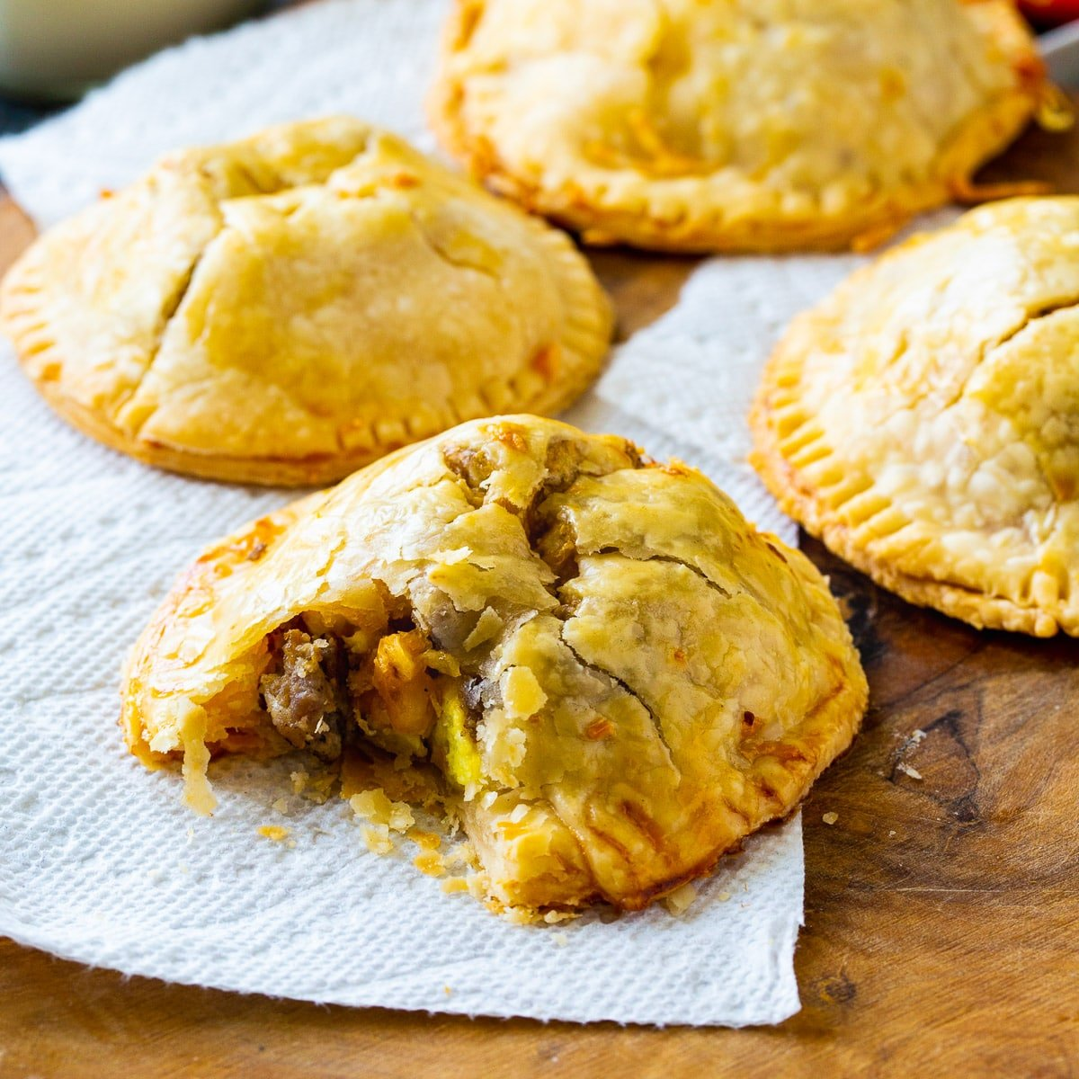 Hand Pies on a wooden board with bite out of one.