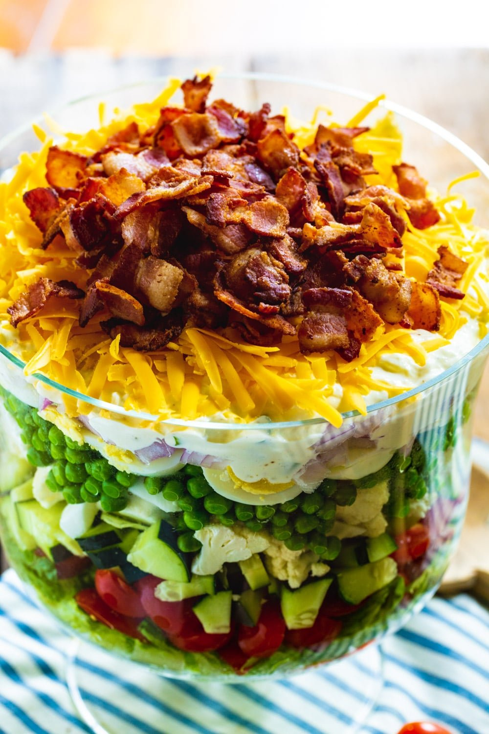 Layered Salad topped with cheese and bacon in a trifle dish.