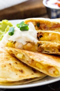Shrimp, Bacon, and Corn Quesadilla on a plate with guacamole and salsa.