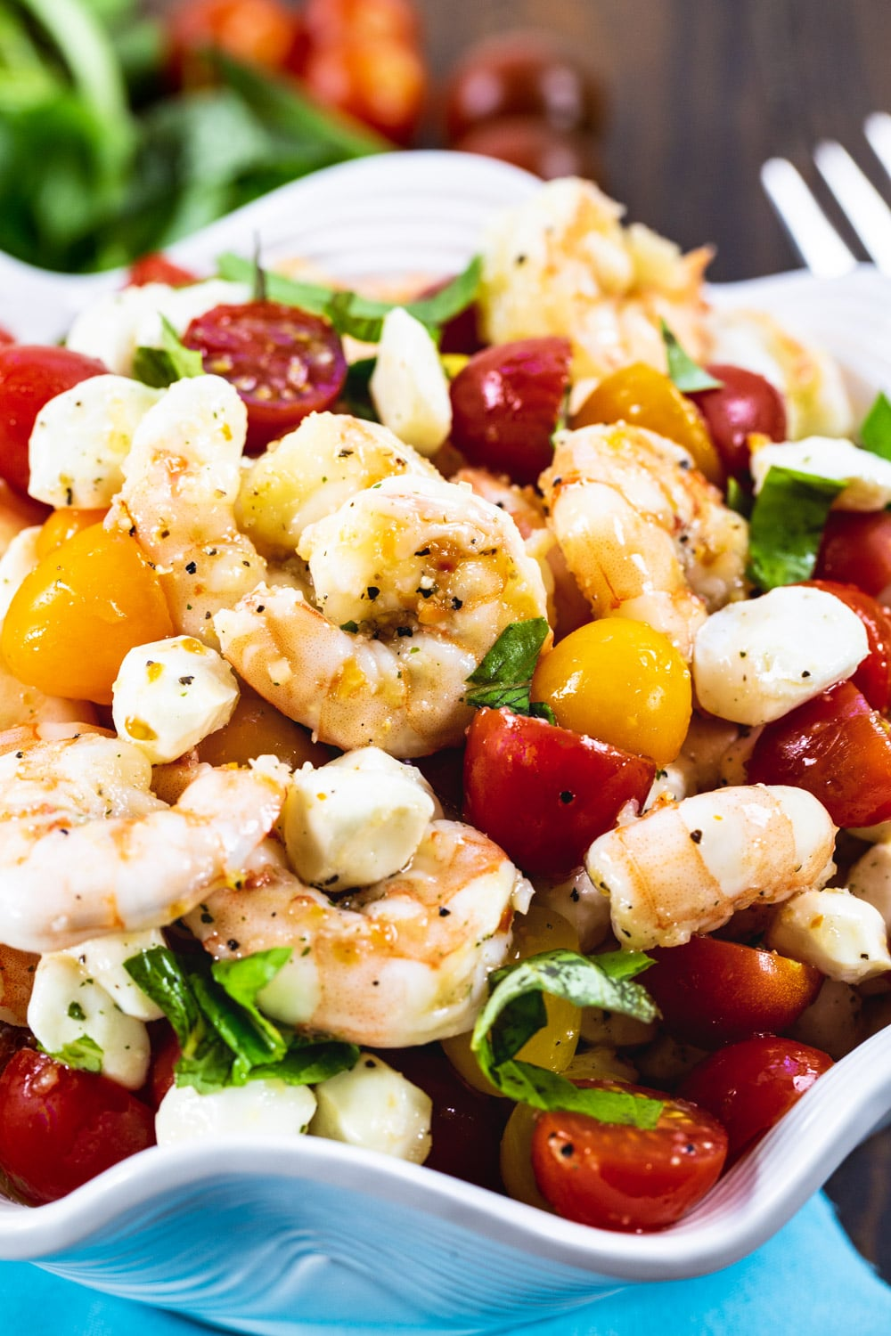 Shrimp Salad with cherry tomatoes and mozzarella balls in white serving bowl.