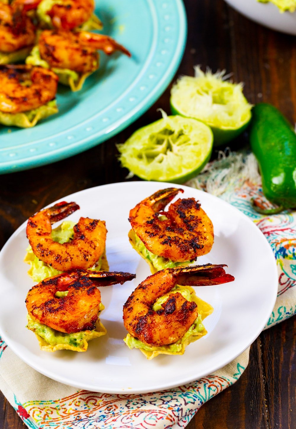 Tostada Bites topped with shrimp on a plate with lime halves.