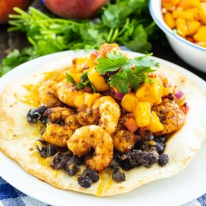 Tostada on a plate topped with black beans, shrimp, and cilantro.