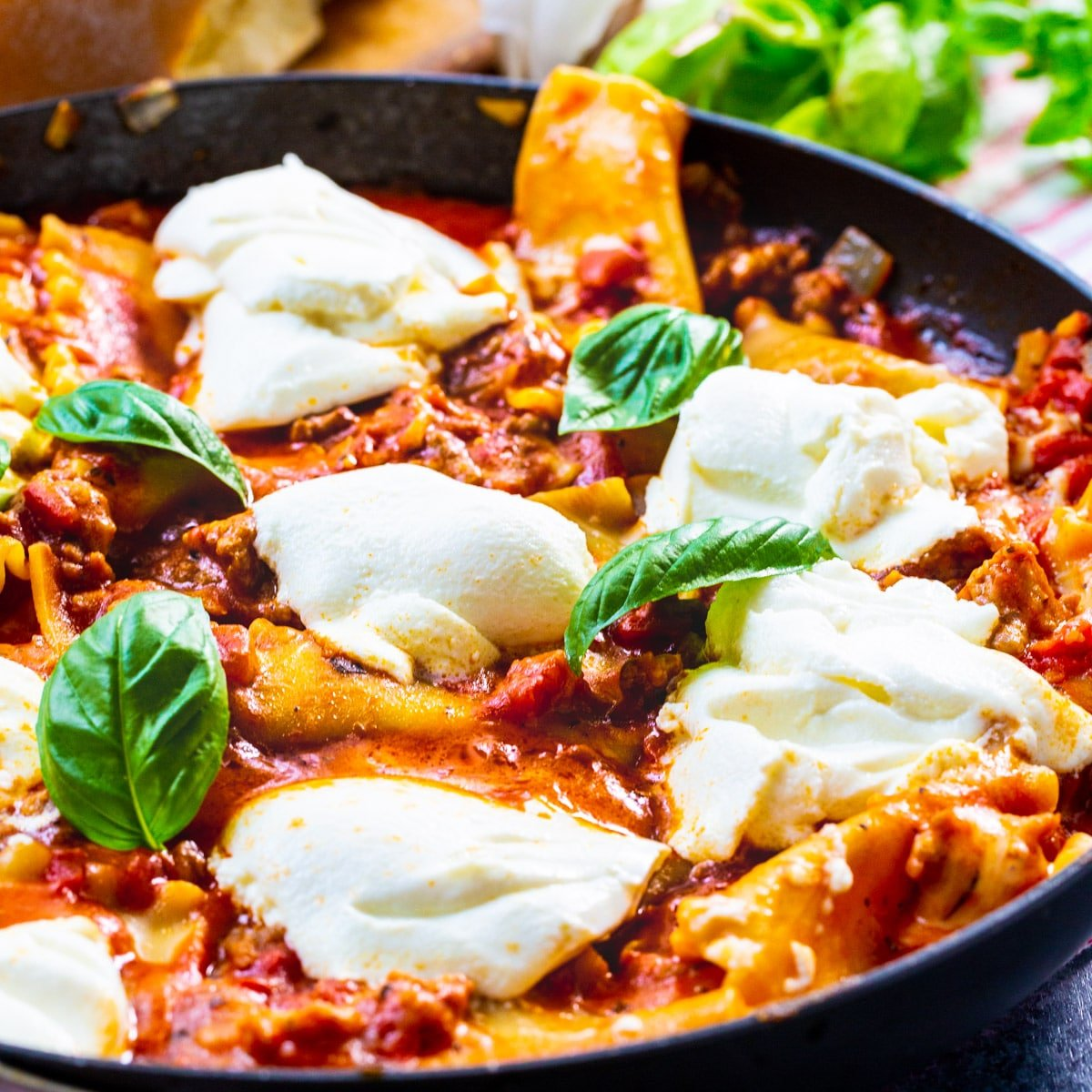 Skillet Lasagna in skillet topped with fresh basil.