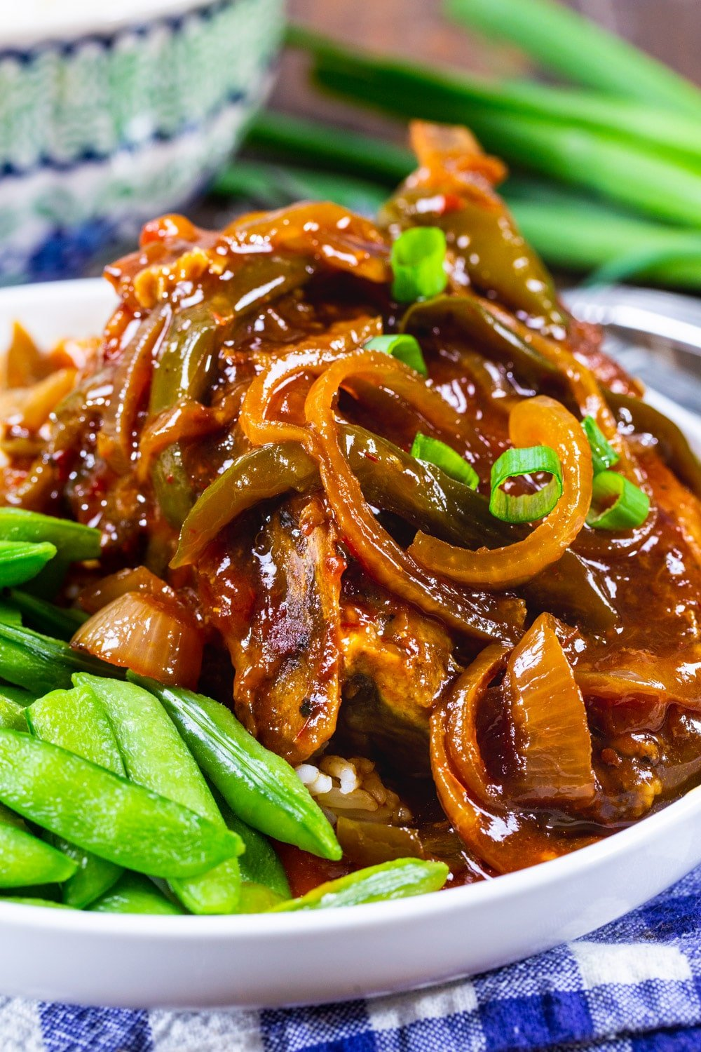 Sweet and Tangy Asian Pork Chops on a plate with sugar snap peas.