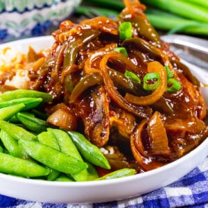 Slow Cooker Sweet and Tangy Pork Chops on a plate with sugar snap peas.