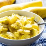 Cheesy Squash in a white bowl with yellow squash in the background.