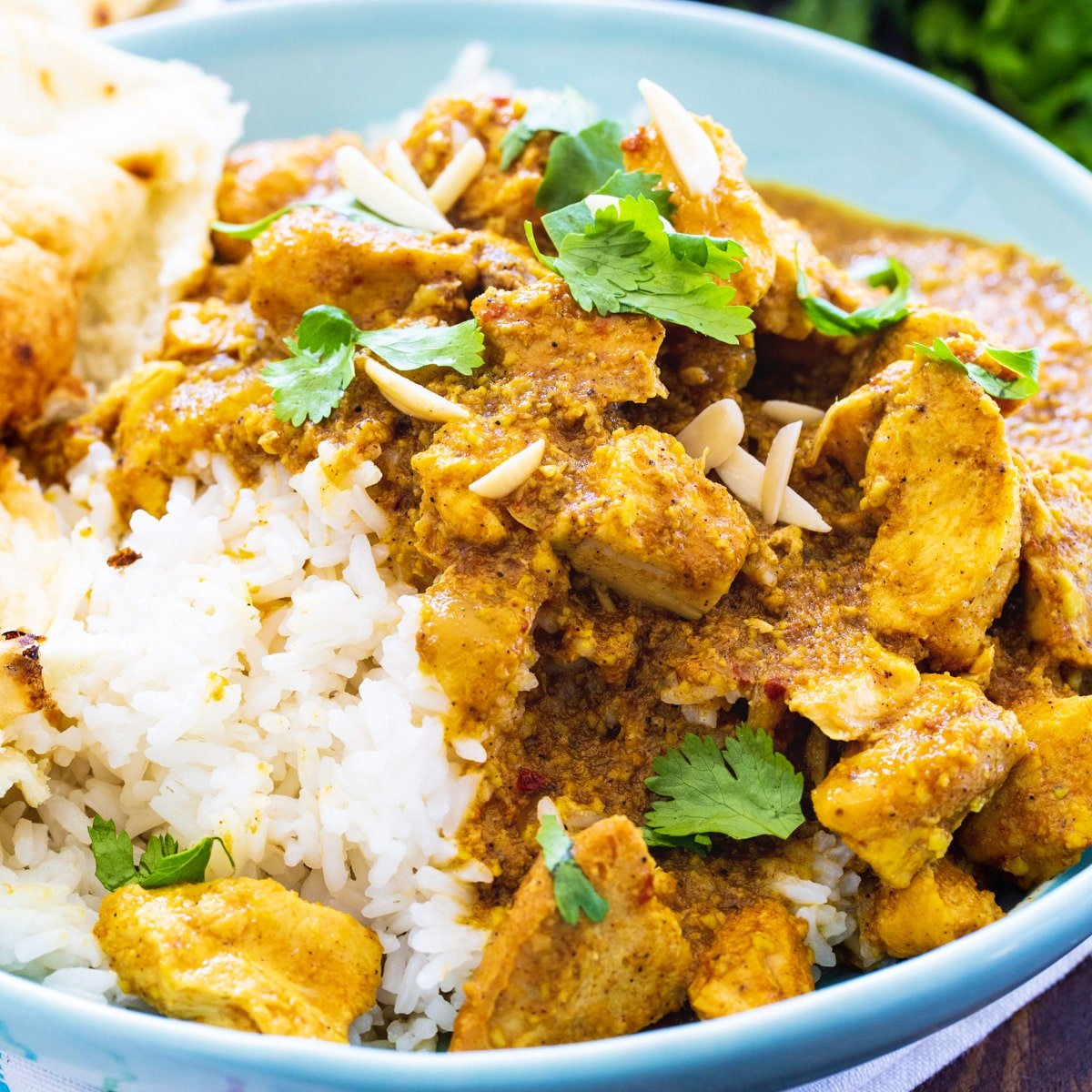 Slow Cooker Chicken Korma over rice in a blue bowl.