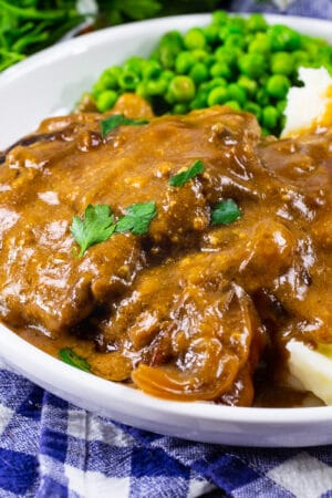Crock Pot Cubed Steak with Gravy on a plate with mashed potatoes and peas.