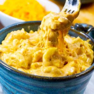 A fork scooping up Slow Cooker Ultra Creamy Mac and Cheese.