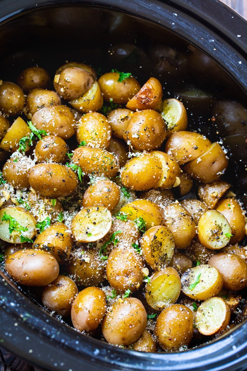 Slow Cooker Garlic Parmesan Potatoes in black crock pot.
