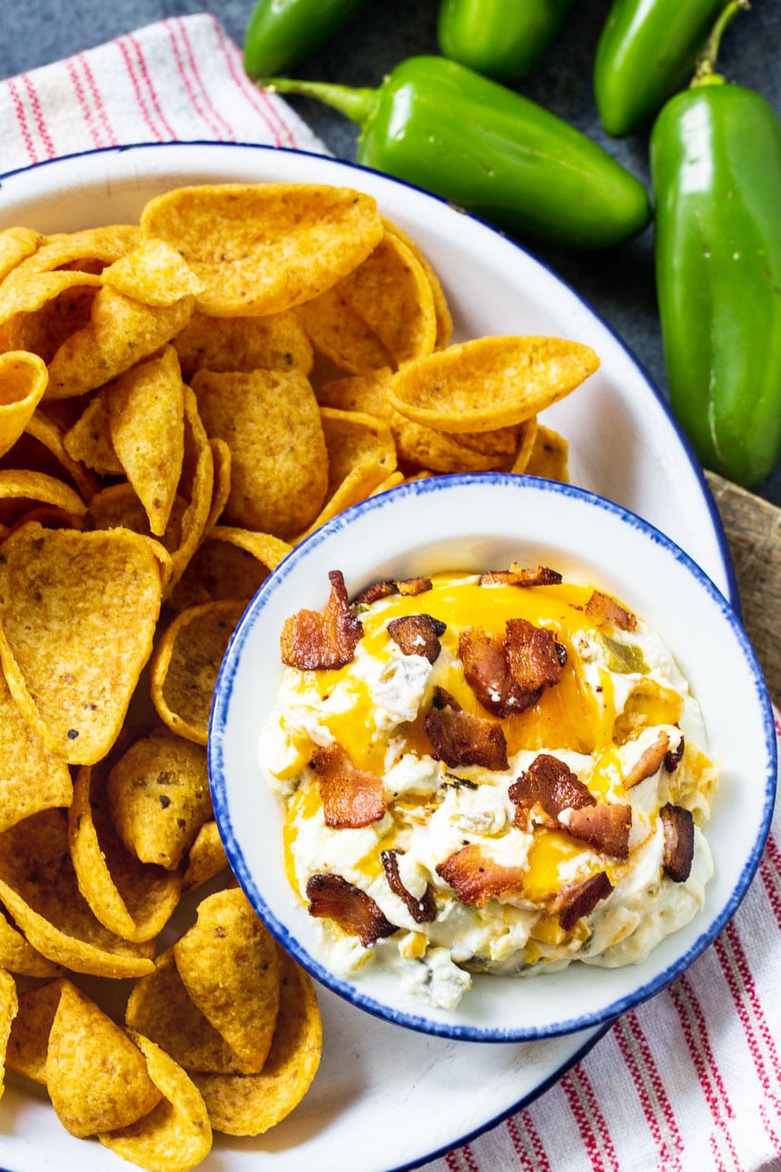 Dip in a bowl on a plate with corn chips.