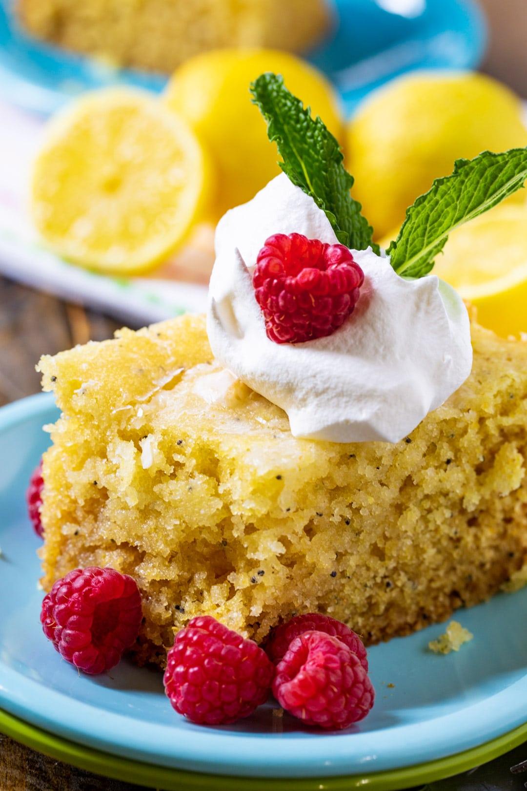 Slice of lemon cake on blue plate with fresh raspberries.