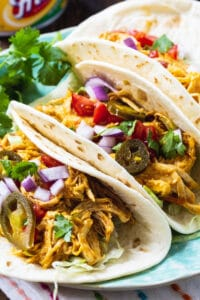 Slow Cooker Nacho Chicken in soft shell tacos.