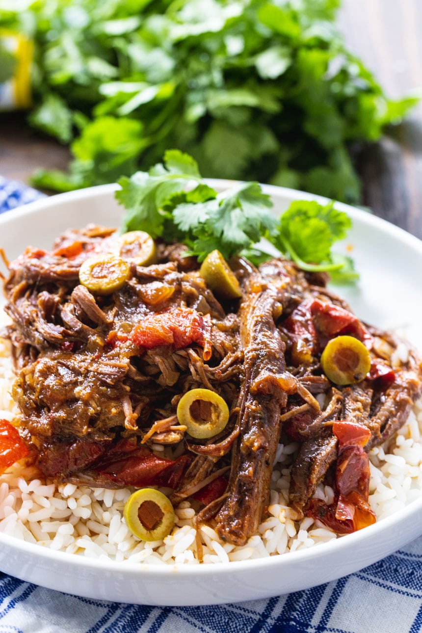 Slow Cooker Ropa Vieja served over white rice with fresh cilantro