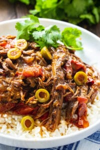 Slow Cooker Ropa Viejo over rice on a plate.