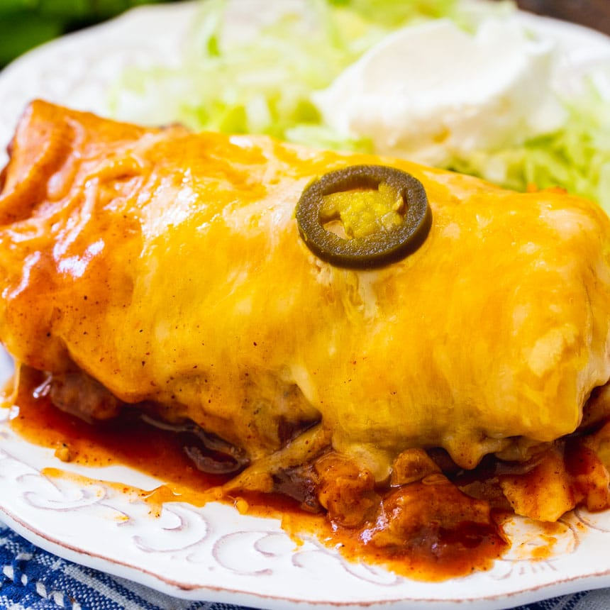 Slow Cooker Smothered Burrito on a plate with iceberg lettuce.