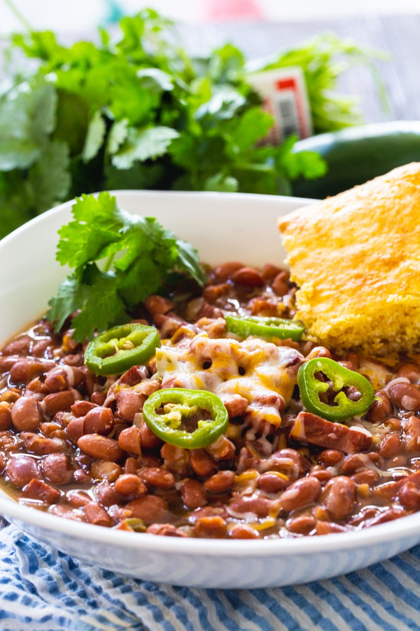 Slow Cooker SPicy Pinto Beans in a white bowl with cornbread.
