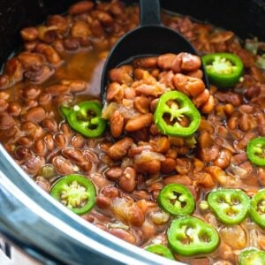 Spicy Pinto Beans in a crock pot with jalapenos on top