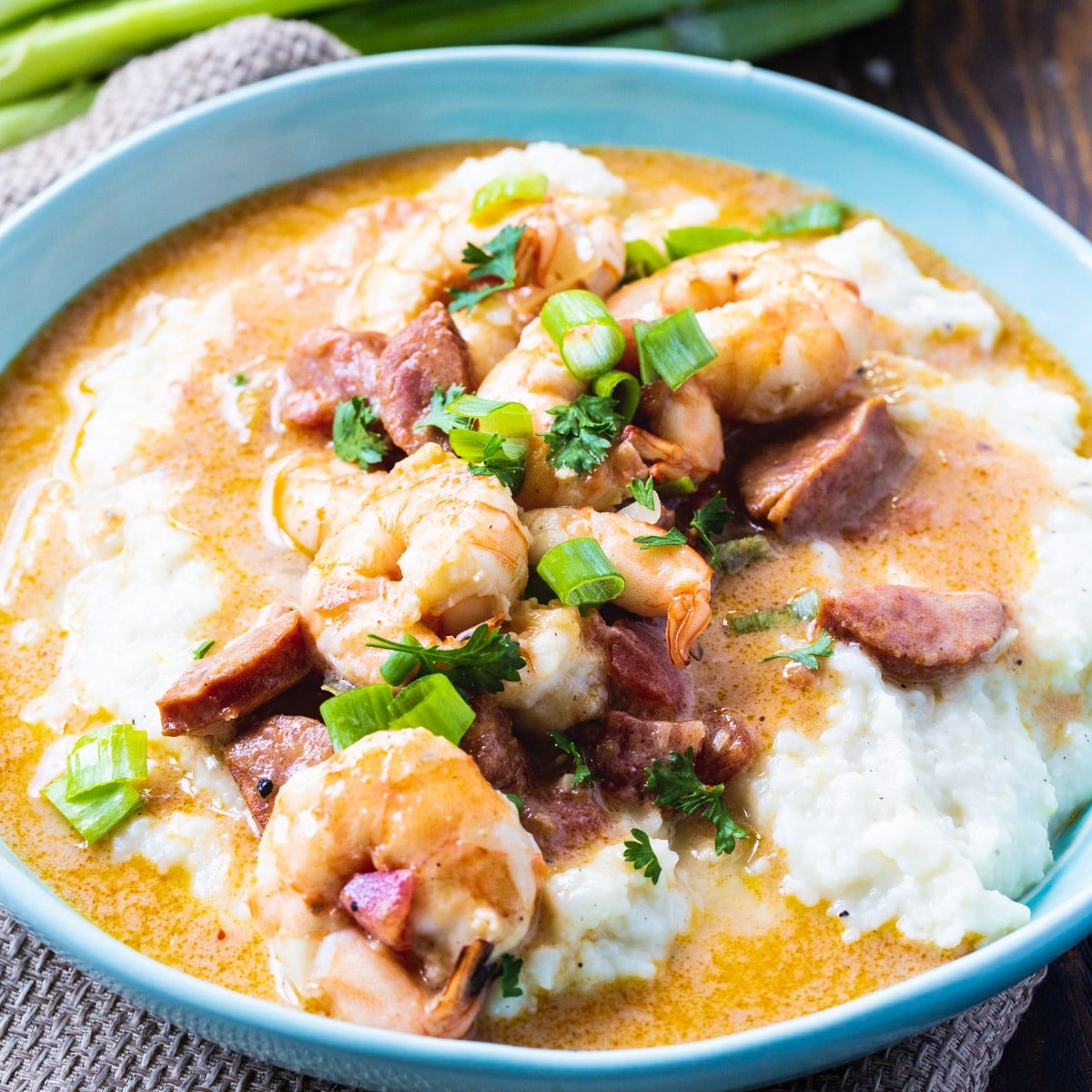 Smothered Shrimp and Parmesan Grits in a blue bowl.