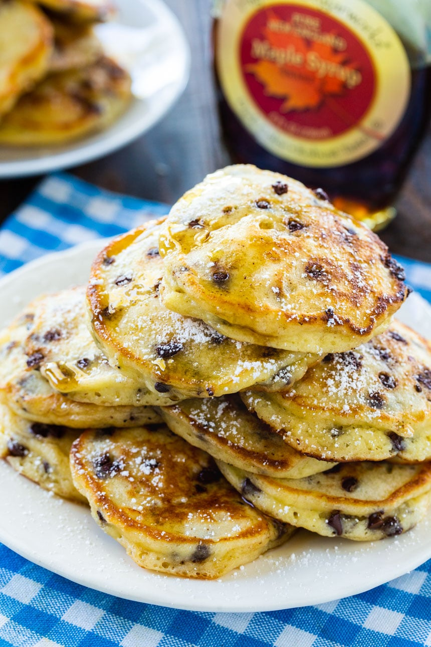 Sour Cream Pancakes on a plate with maple syrup in background.