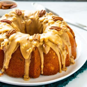 Bundt Cake covered with praline sauce on large white serving platter.