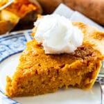 Slice of Southern Sweet Potato Pie topped with whipped cream.