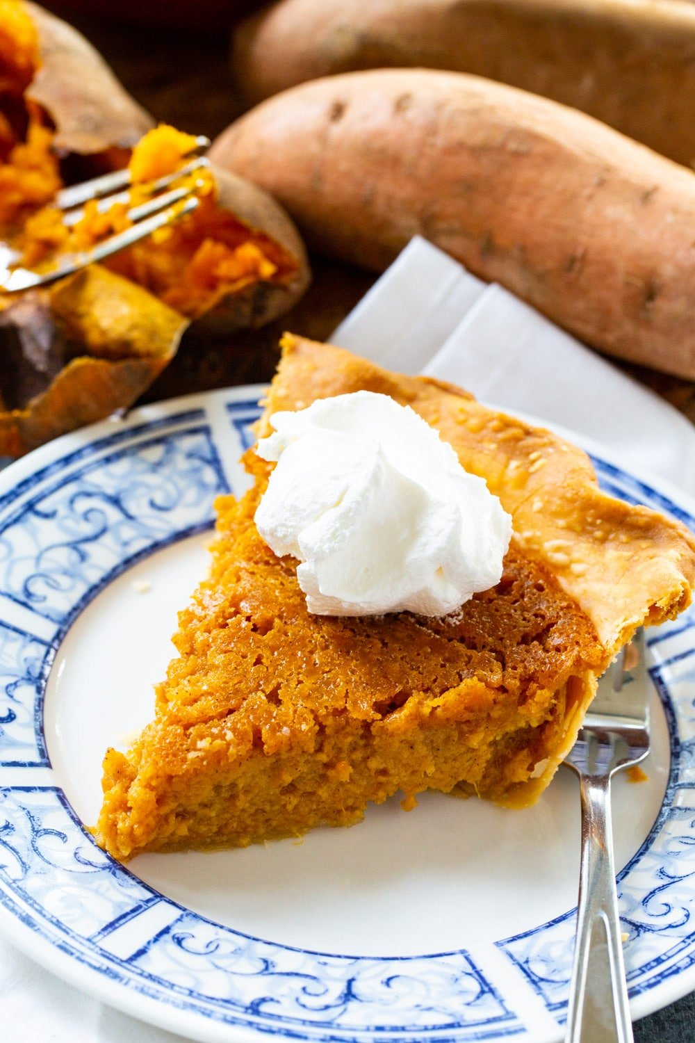 Slice of pie on a plate with sweet potatoes in background.
