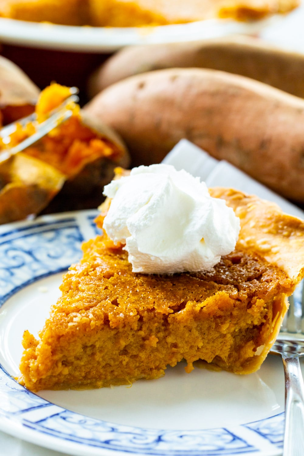 Southern Sweet Potato Pie slice topped with whipped cream.